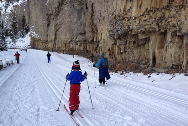 cross country skiers in front of basalt pillars on the Tower Falls Ski Trail in Yellowstone