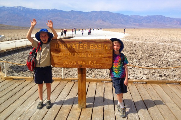 "Two boys next to a ""Badwater Basin"" sign."