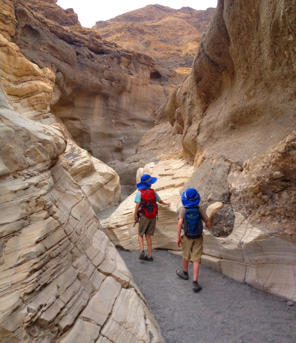 Two boys walking through rock walled Mosaic Canyon.