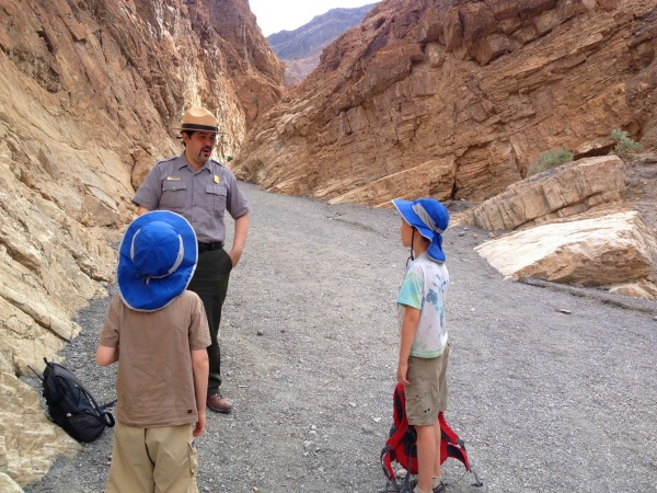A Ranger talking to two boys in a canyon.