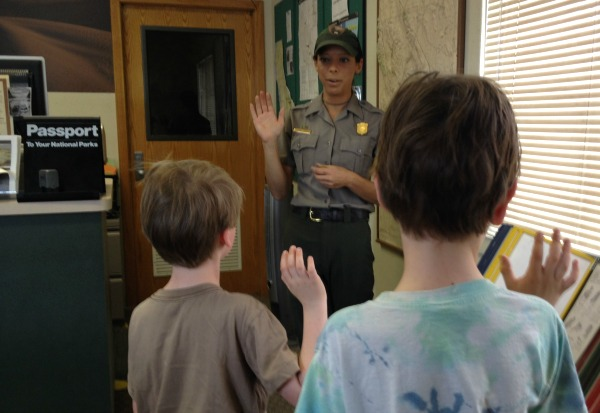 A Park Service Ranger performing the Junior Ranger oath.