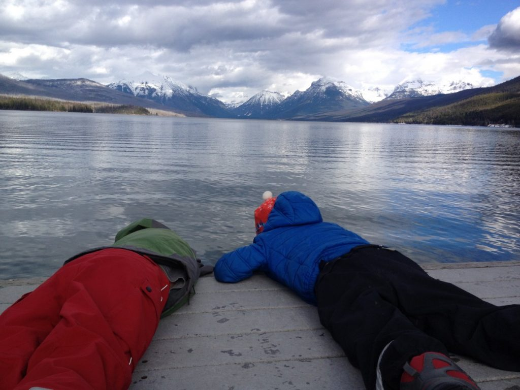 two kids laying on a dock looking at Lake McDonald in Glacier National Park with snowy mountains in the distance