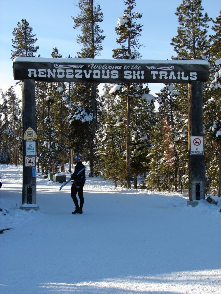 "sign reading ""Rendezvous Ski Trails"" with Nordic skiers below. In West Yellowstone Montana"