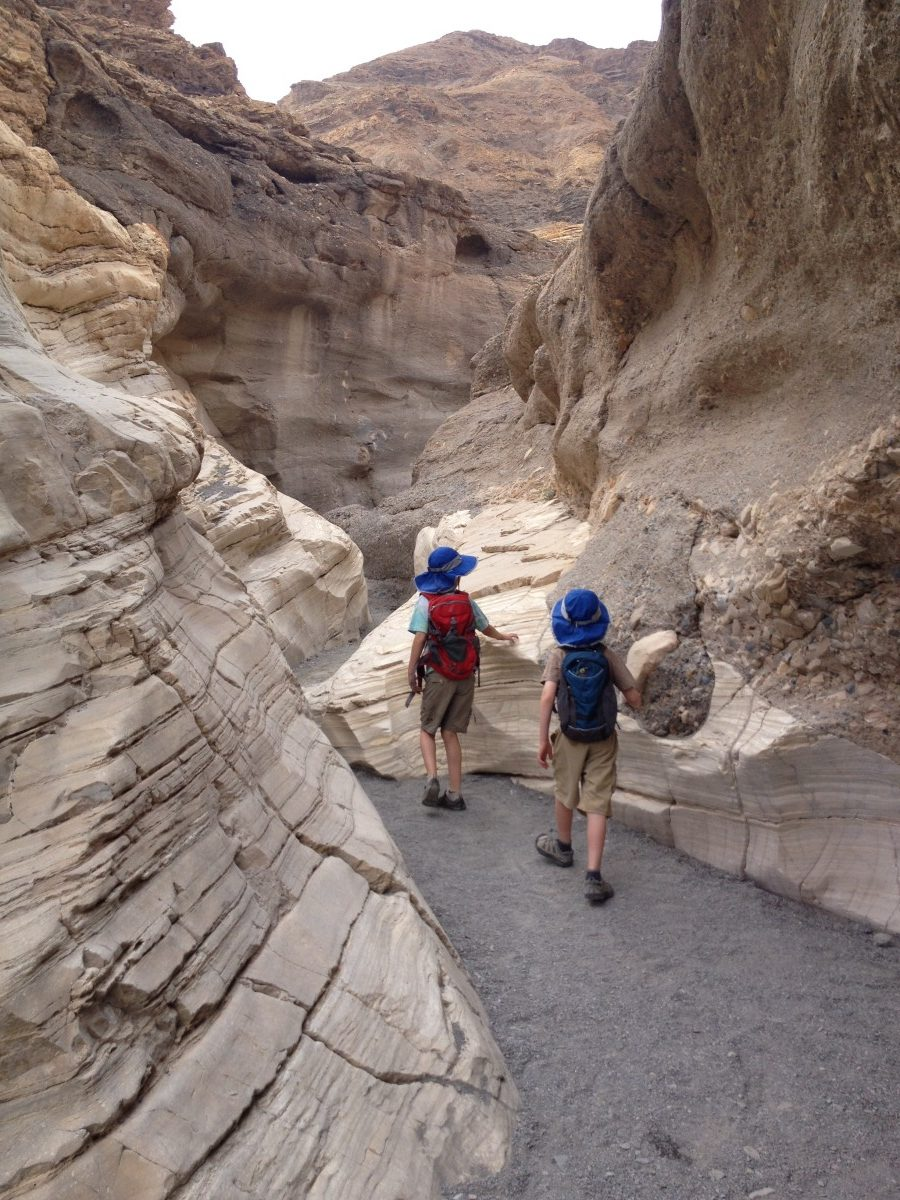 Two boys walking in the narrows of Mosaic Canyon Death Valley