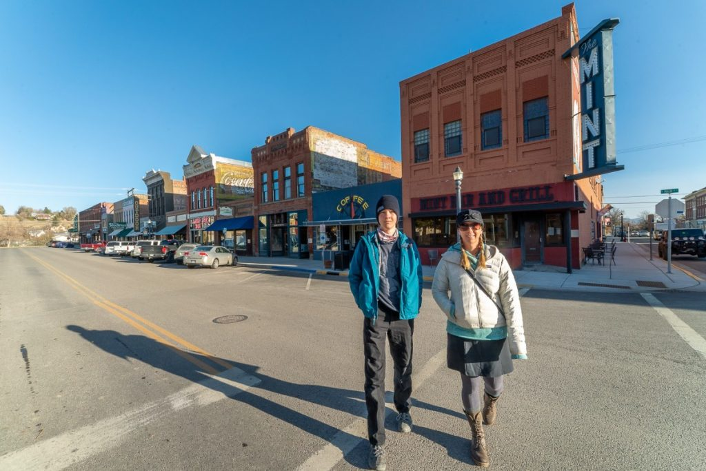 two people walking in front of brick buildings for things to do in Livingston Montana