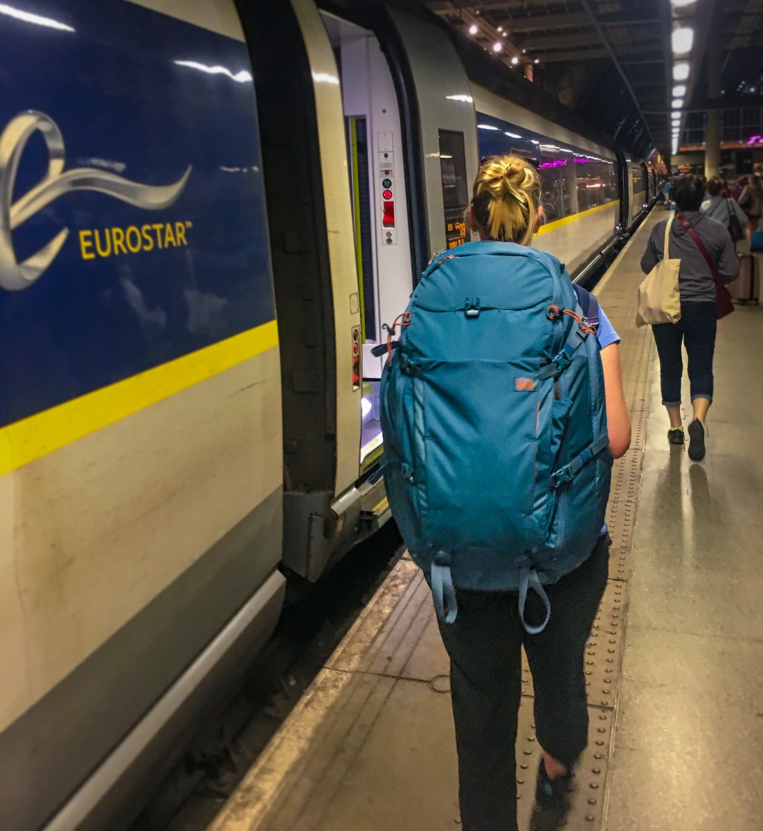 Woman with REI Women's Ruckpack Travel Backpack next to Eurostar train in London