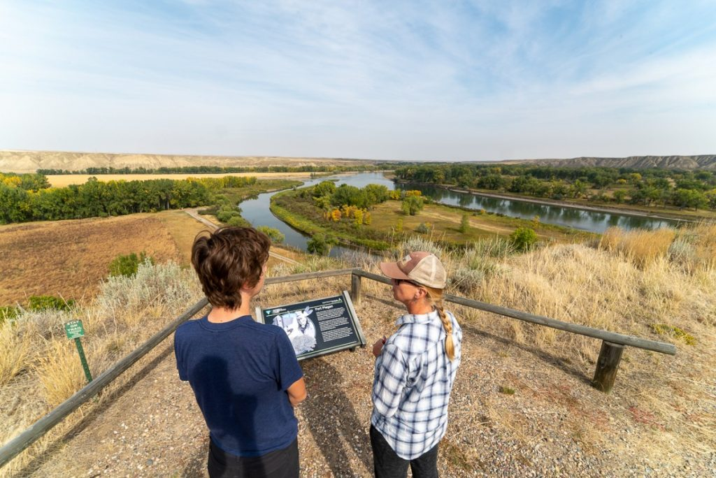 Two people standing at Decision Point on the Lewis and Clark Trail in Montana overlooking a river.