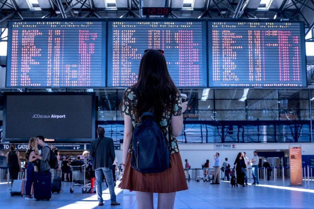 woman in airport looking at flight screen