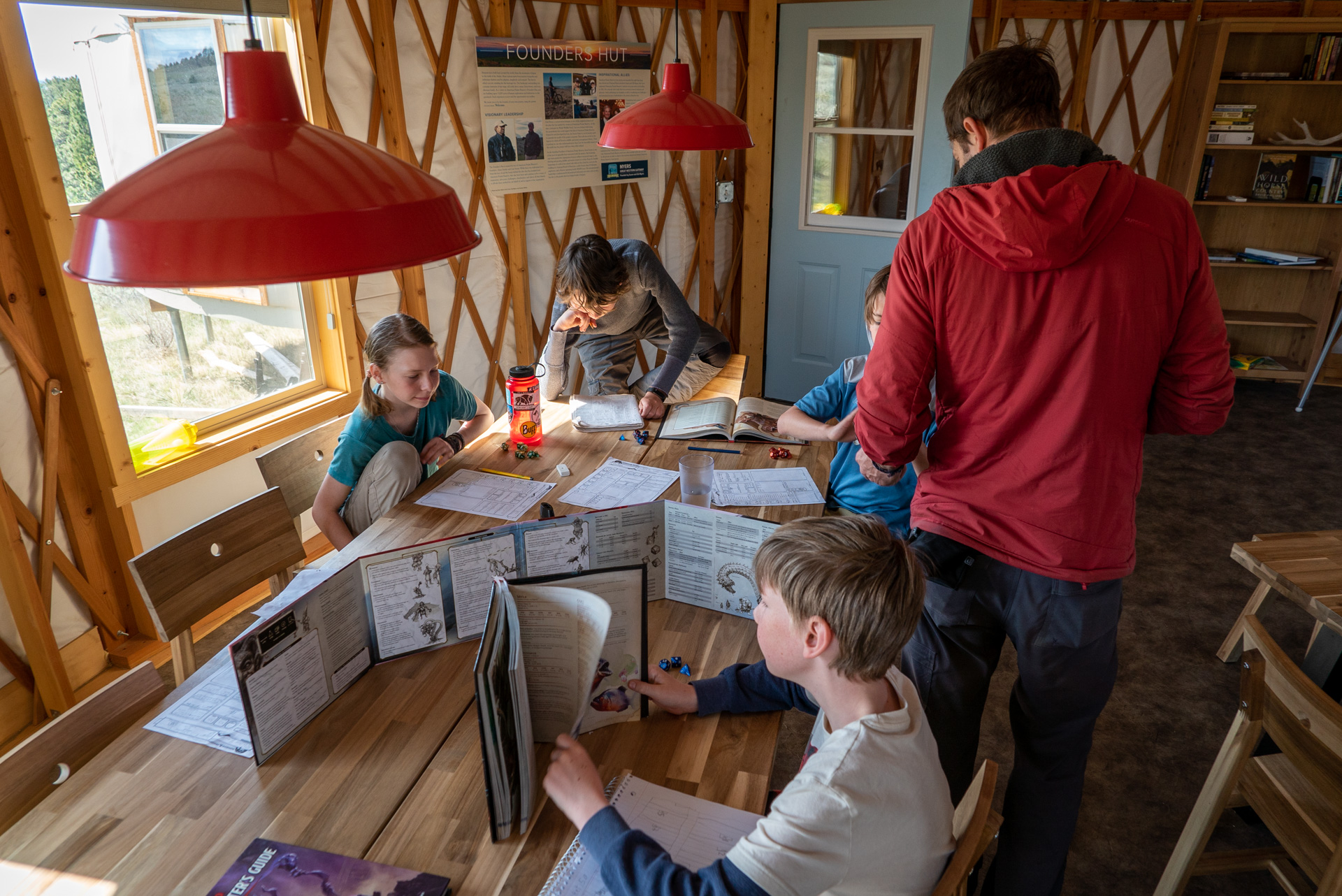 Family playing games inside a yurt on the American Prairie Reserve