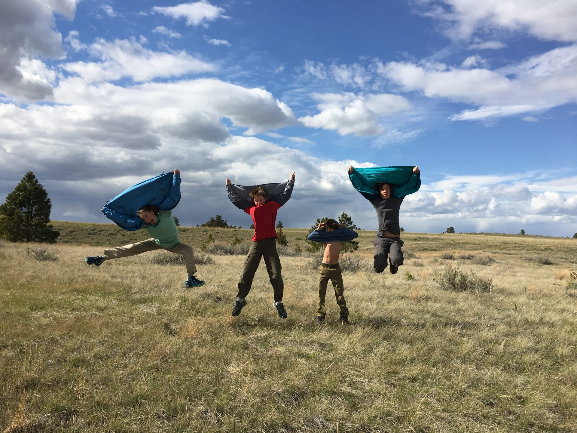 four kids jumping in the air with jackets over their heads on American Prairie Reserve