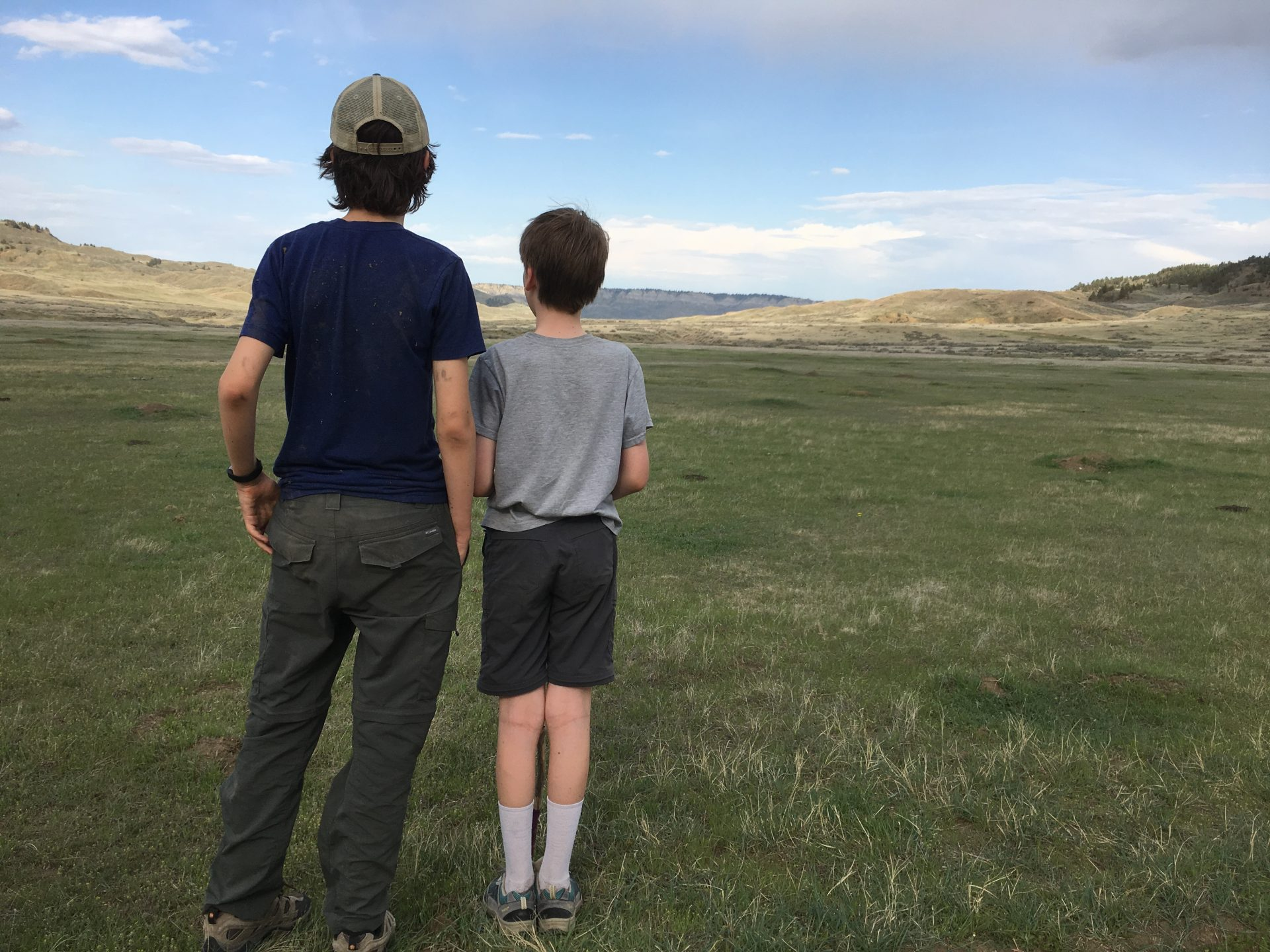 backs of two kids looking at unique places to visit in Montana like American Prairie Reserve