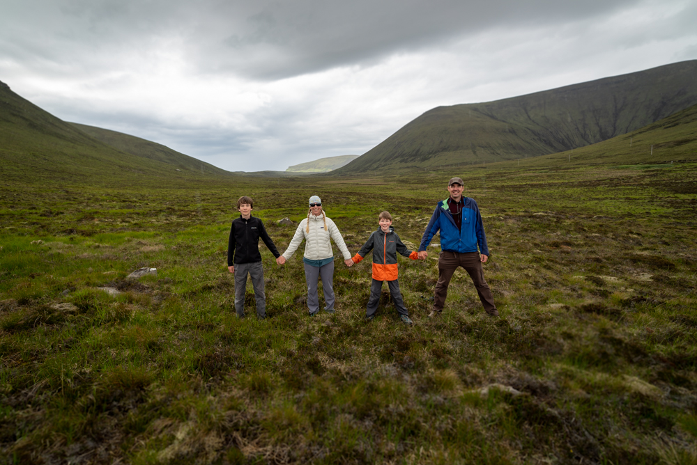 Family photo of four people near the DWarfie Stane on Hoy