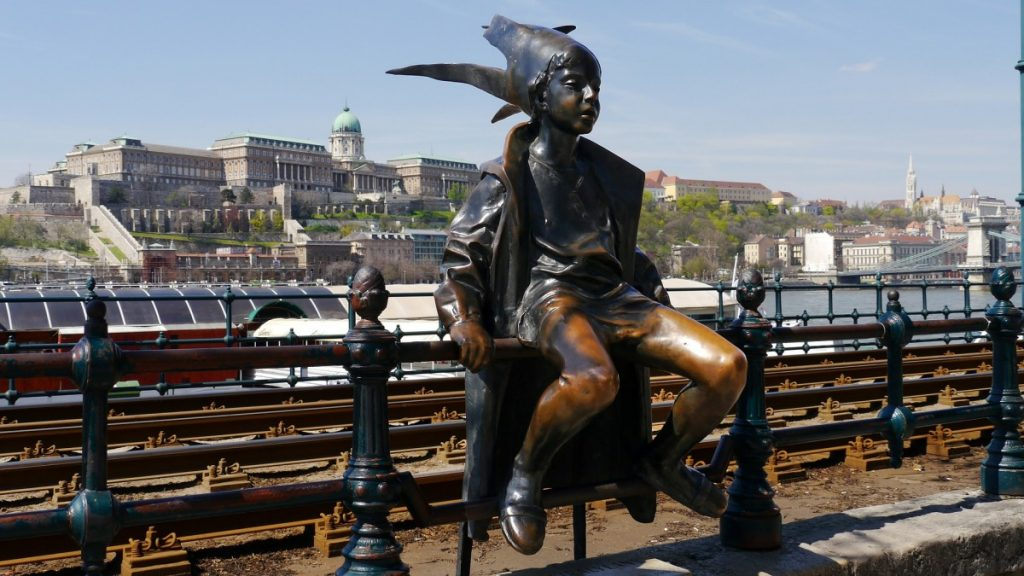 bronze statue of a boy sitting on a rail in Budapest