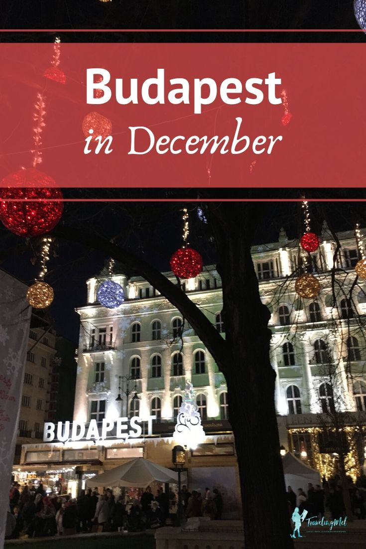 "white building behind a ""Budapest"" sign and a tree with lights. Text, ""Budapest in December"