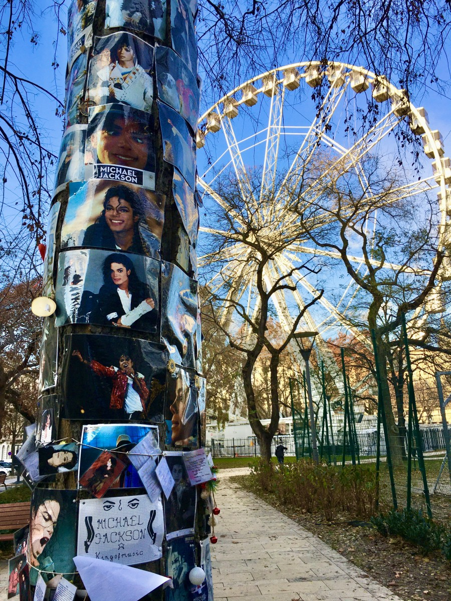 michael jackson pictures on a tree and a ferris wheel in the back in Budapest
