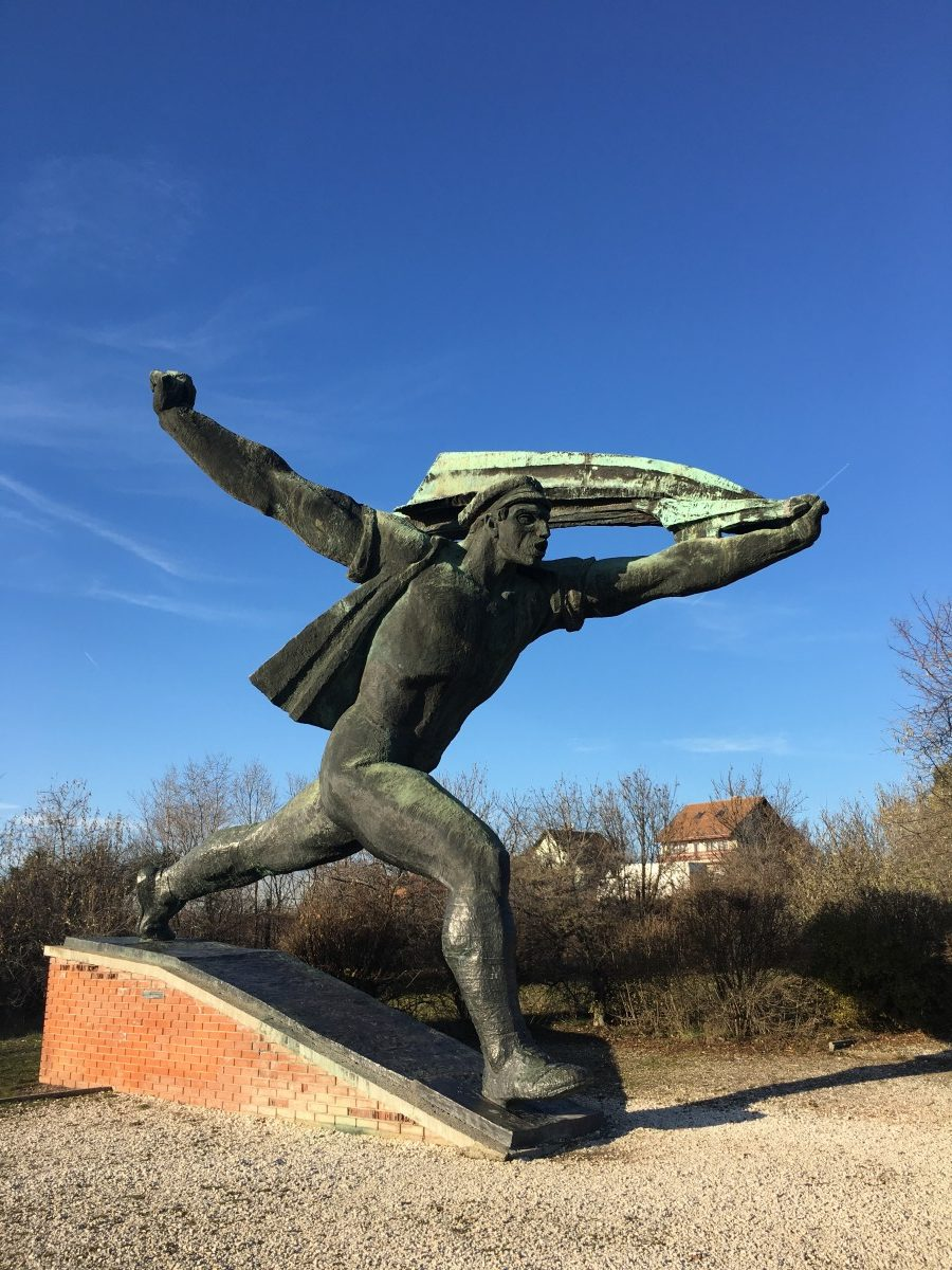 statue of a Soviet man running with a cloth over his head in Memento Park Budapest