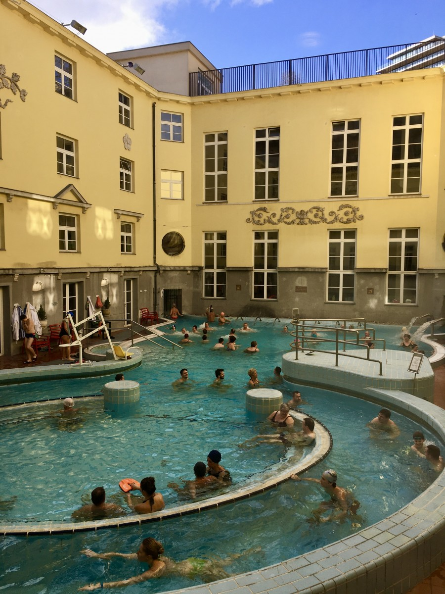 pool with lots of people and yellow walls