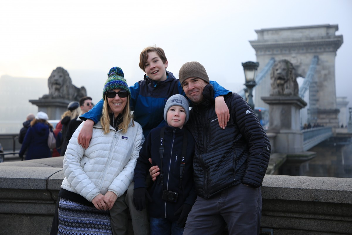 family photo of two adults and two kids standing on a bridge