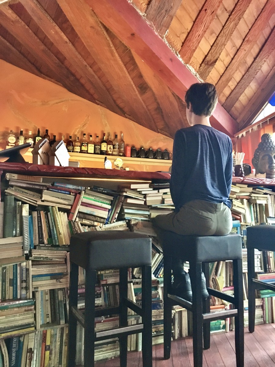 boy sitting at bar held up by books