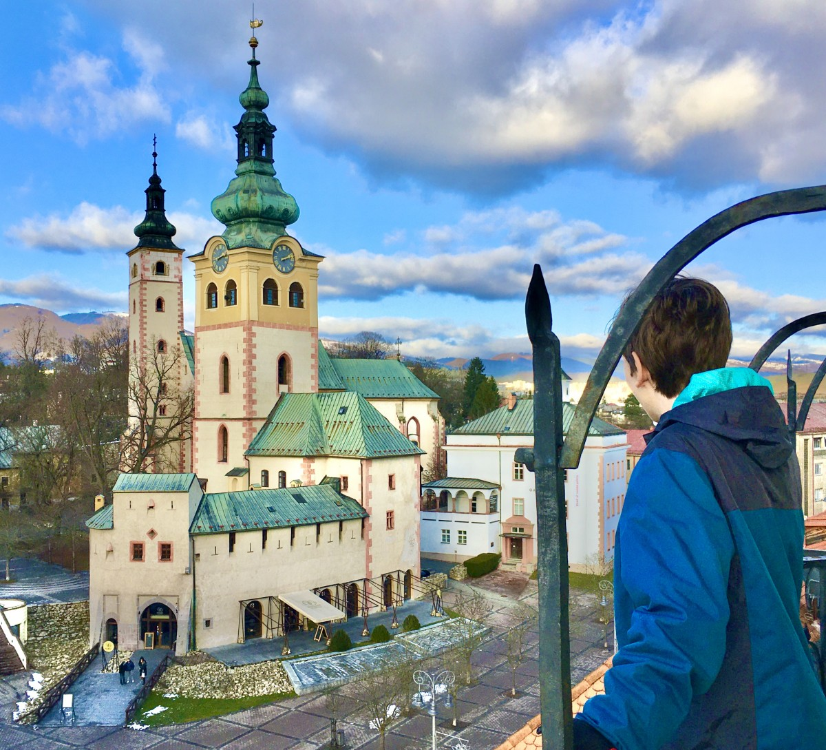 boy in a clock tower overlooking the Banska Bystrica castle