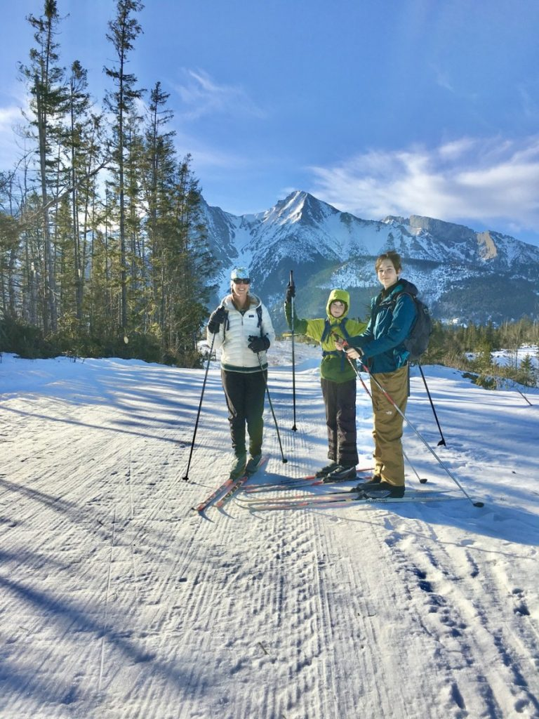 mom and two sons on cross country skis with mountains in back