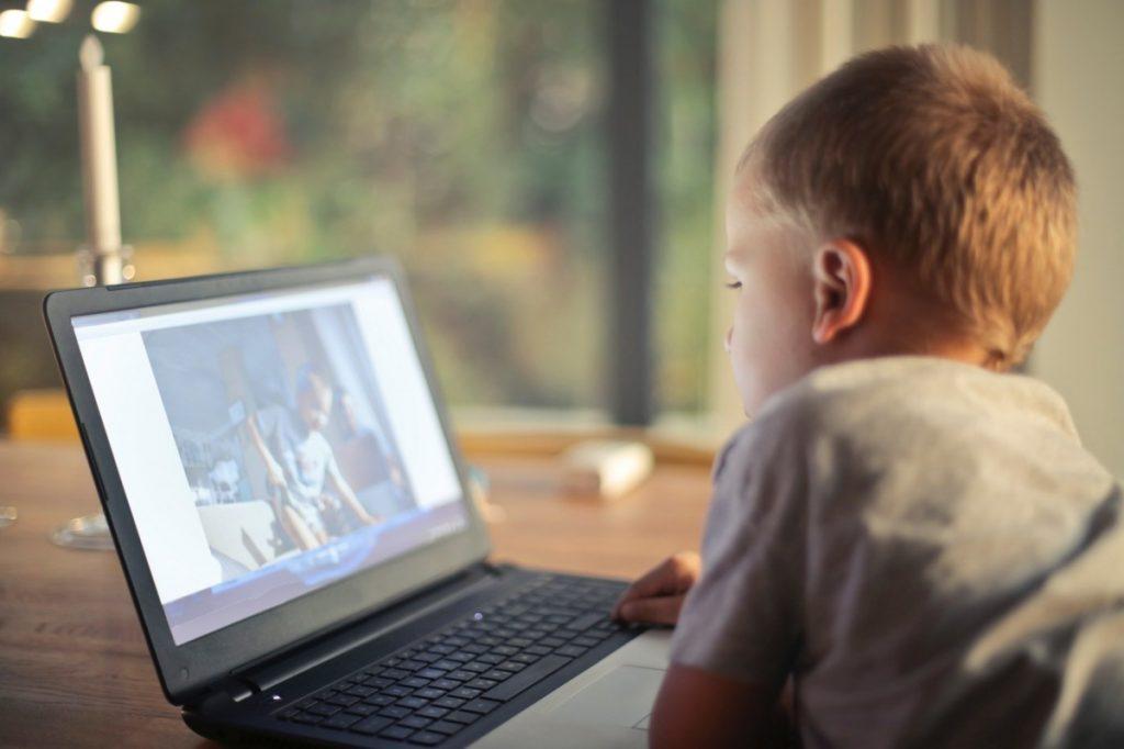 boy watching online homeschool class on laptop