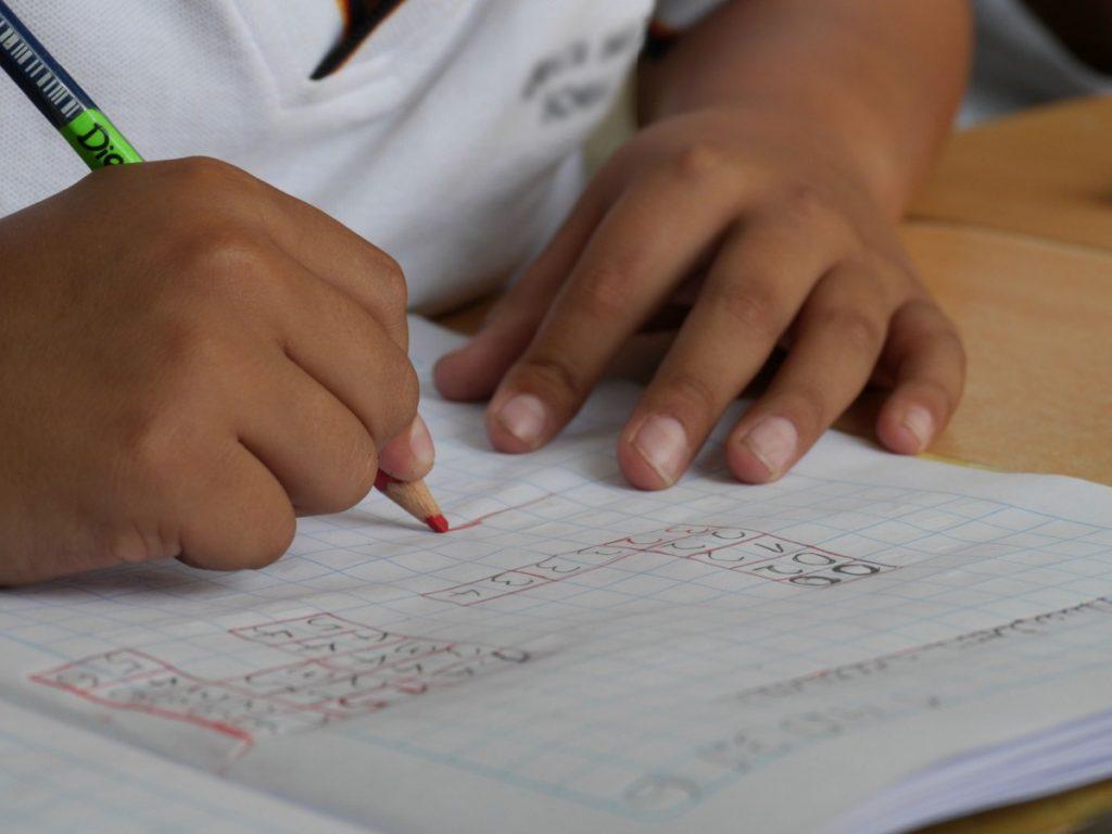child's hands and homeschool math problem