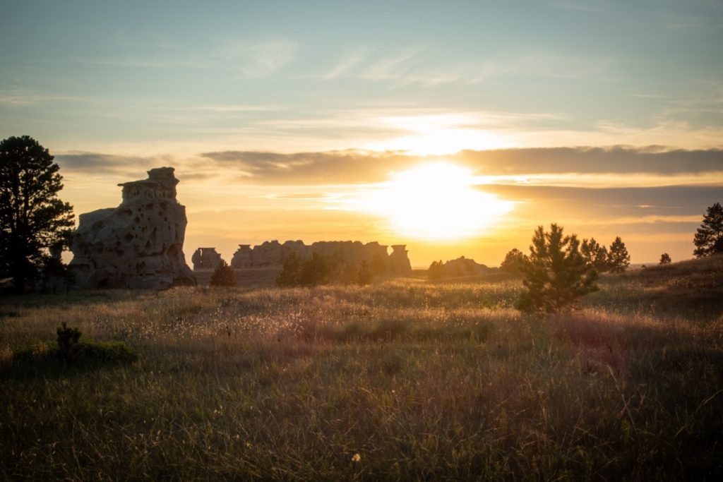 sunrising over medicine rocks state park on the best montana road trip