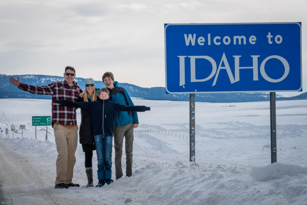"""Family standing by """"Welcome to Idaho"""" sign on an Idaho winter road trip"""