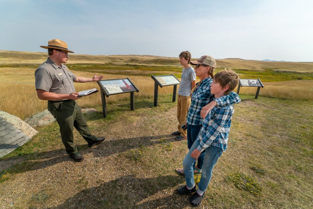 Three people listening to a ranger at Bear Paw Battlefield