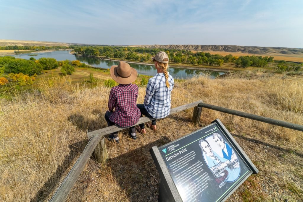 two people sitting overlooking a river at Decision Point a Lewis and Clark site in Montana