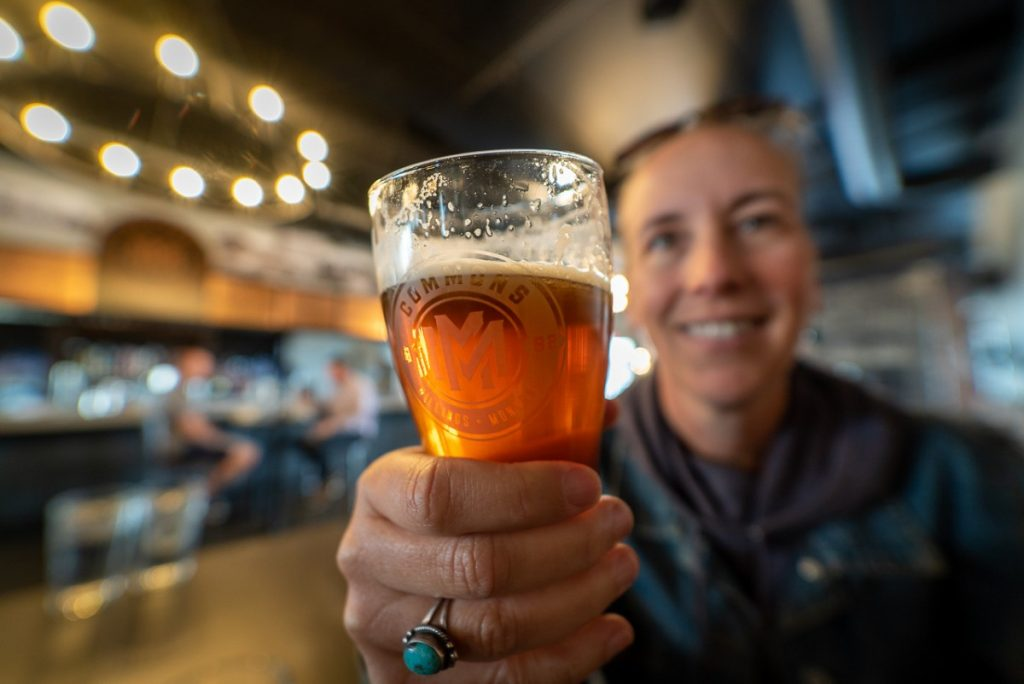 Beer in focus in foreground, smiling woman blurred, holding glass things to do in Billings right now