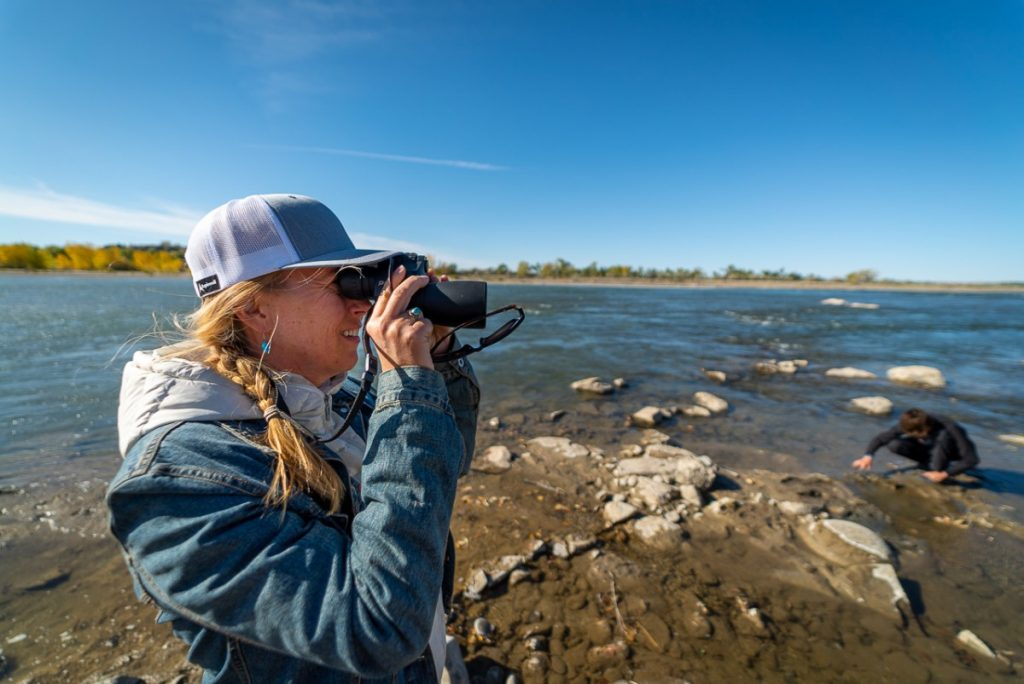 woman holding binoculars and bird watching in Montana