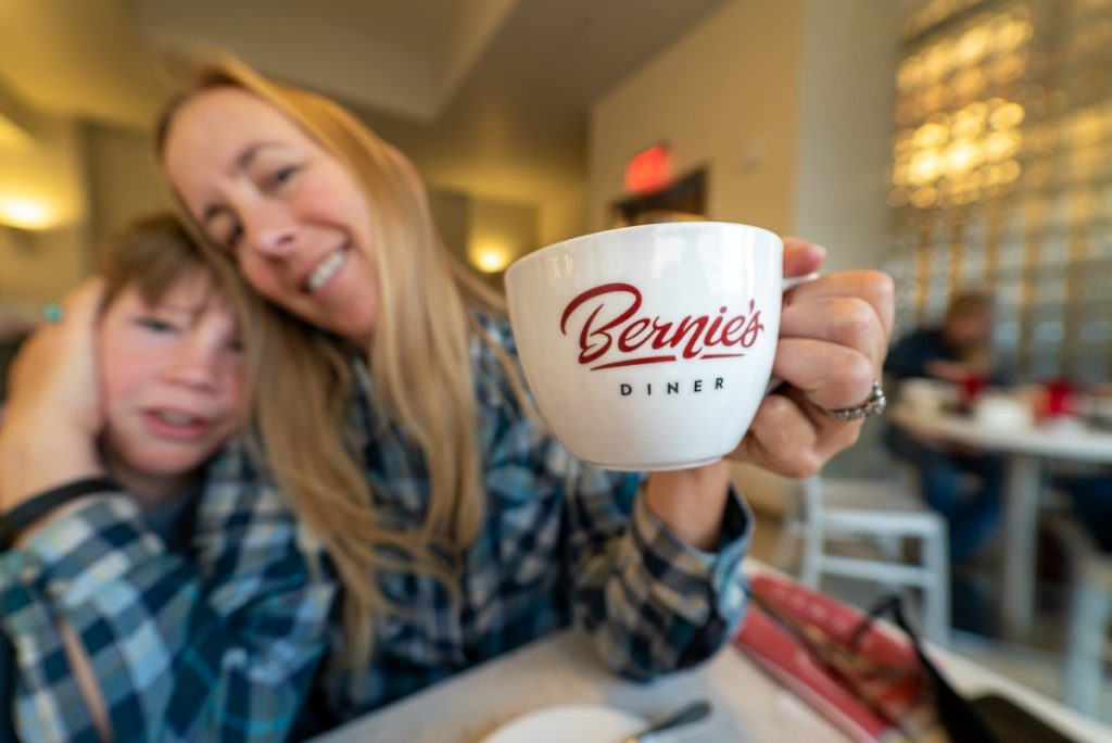 woman and son blurred with coffee cup that reads Bernie's Diner in the foreground