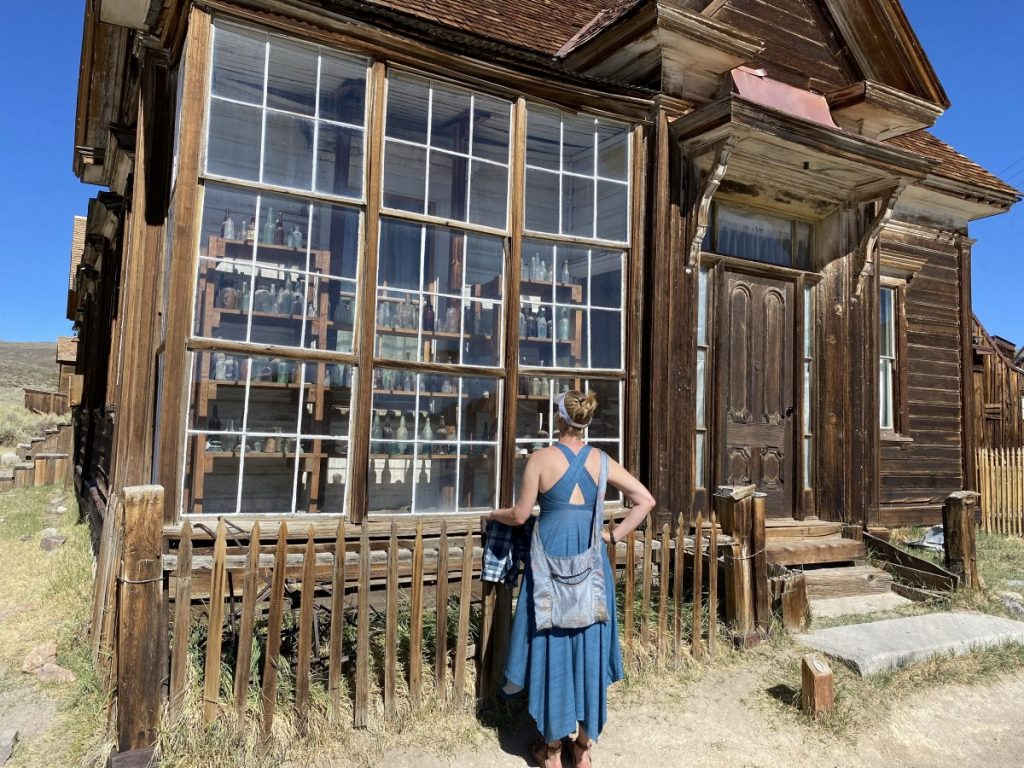 Woman looking in window in Bodie Ghost Town State Park