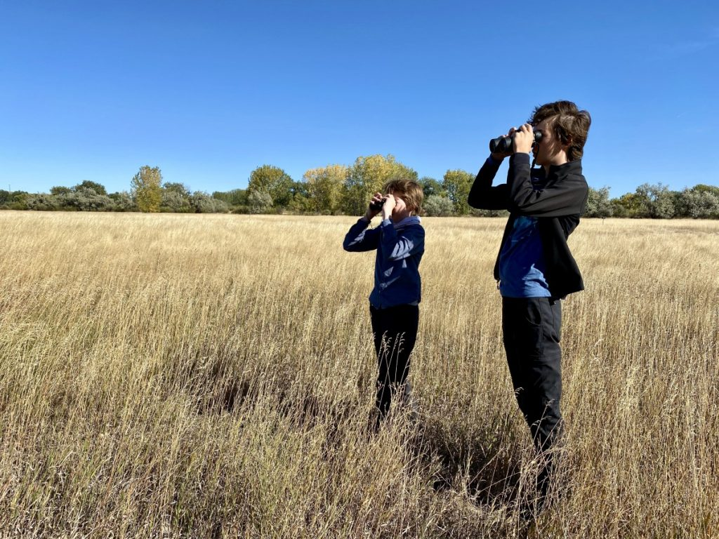 two boys using binoculars on the prairie