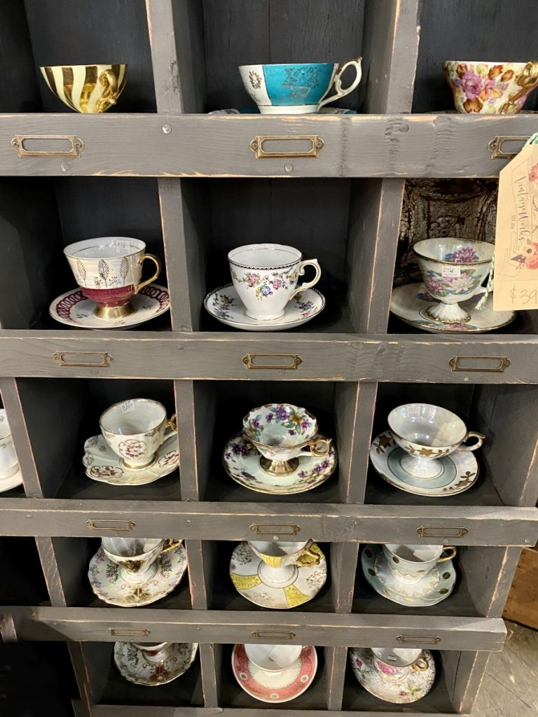 antique tea cups and saucers on a shelf