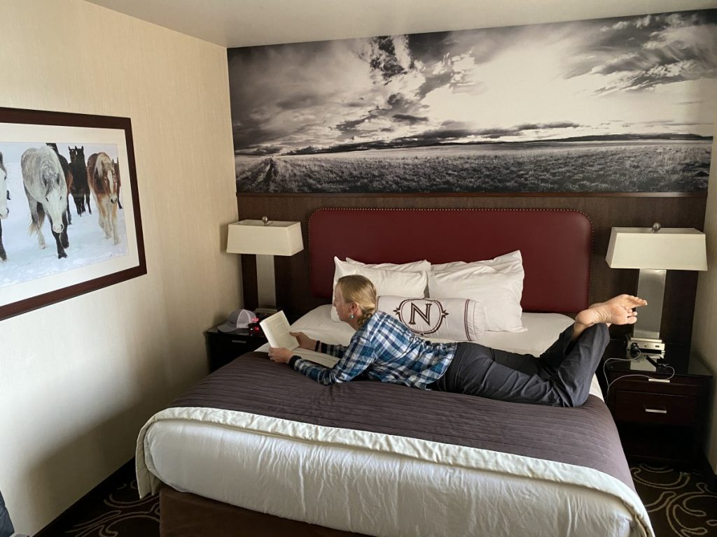woman reading book on bed at Northern Hotel Billings Montana