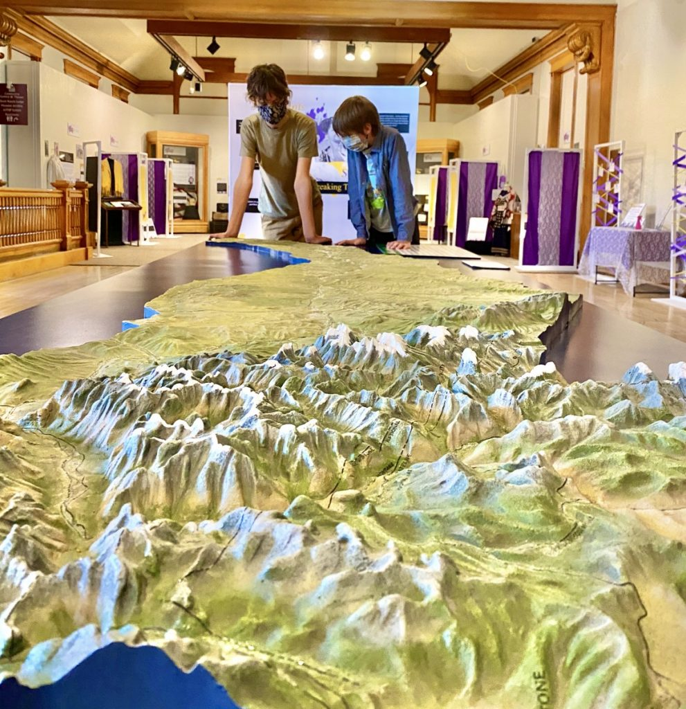 Two teems looking at a relief map of the Yellowstone River Valley