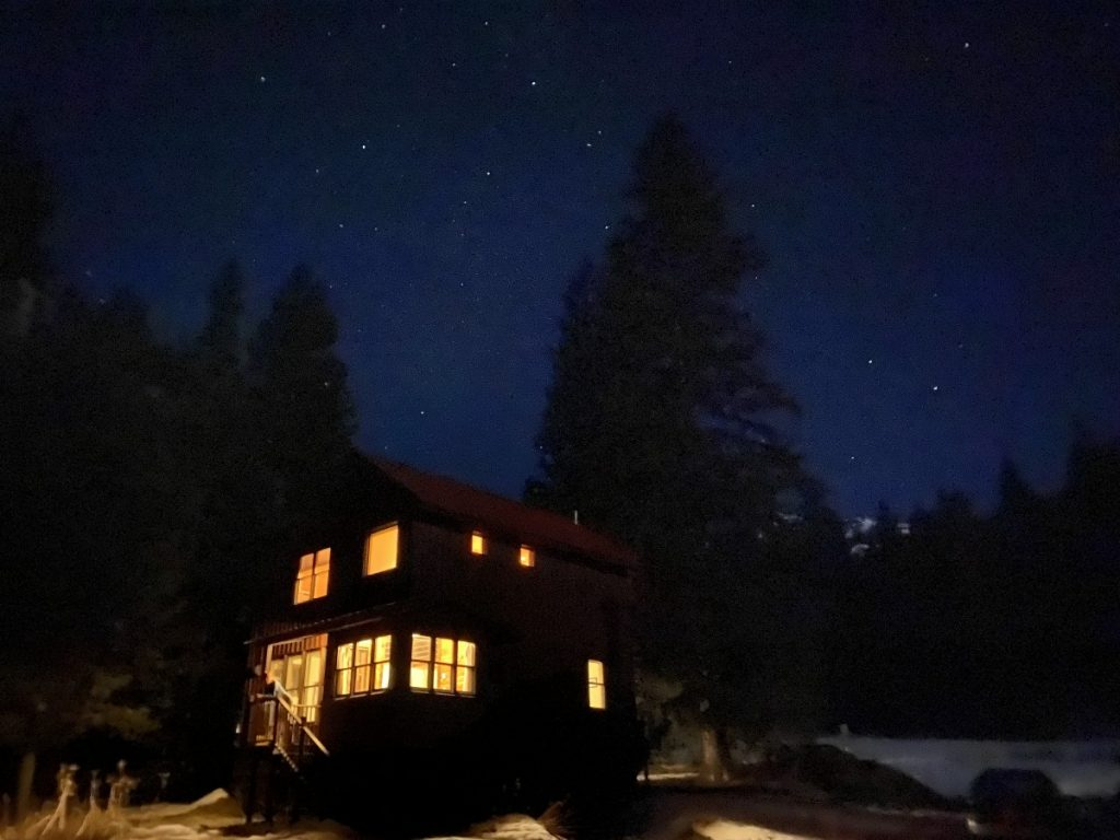 cabin in the woods at night with a starry sky
