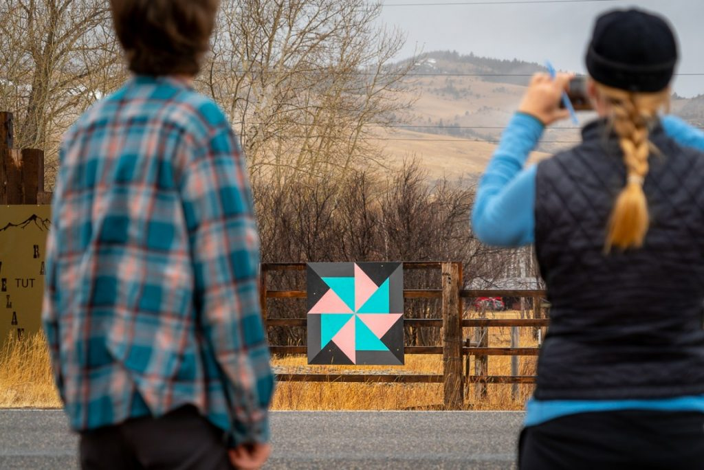 two people looking at a barn quilt square