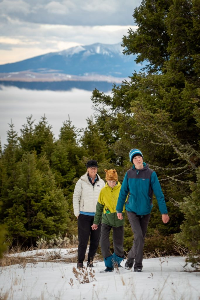 three people walking in the snow on a tree covered mountain with the Crazy Mountains in back