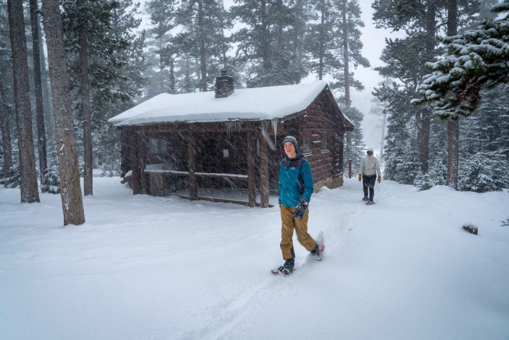 two people snowshoeing by a cabin in Montana