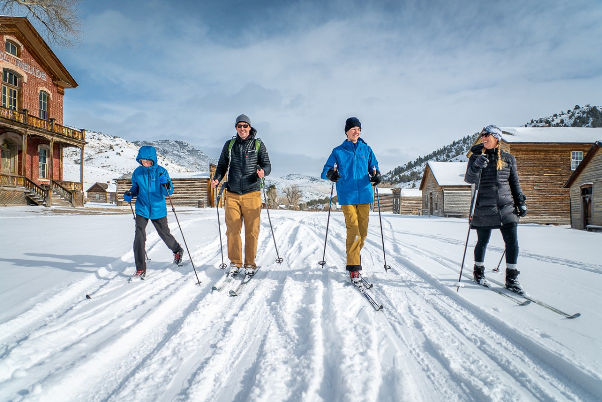 four people cross country skiing in ghost town Bannack State Park Montana