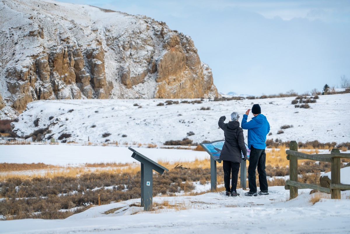 Three people looking at an interpretive sign in front of Beaverhead Rock State Park Montana in winter