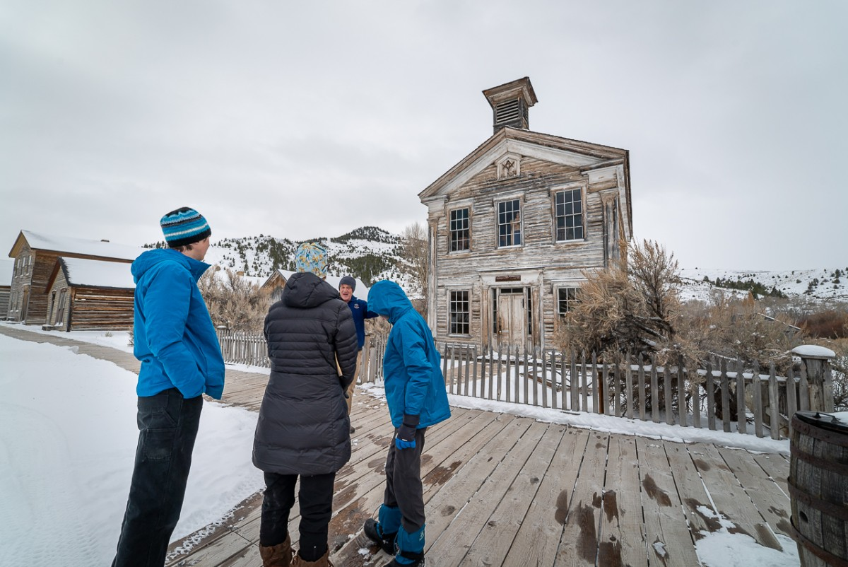 Four people in front of a church in the ghost town Bannack State Park