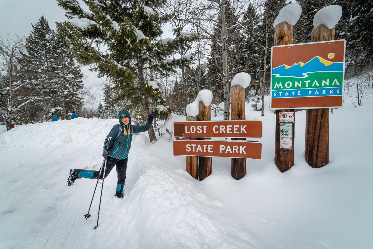 """Woman leaning on a sign reading """"Lost Creek State Park"""" and """"Montana State Parks"""""""