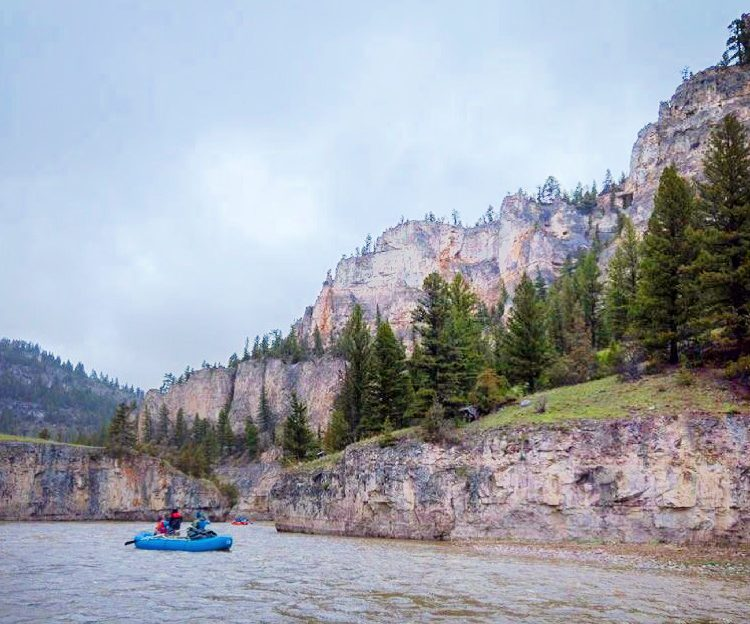 Raft floating beneath limestone cliffs on the smith river