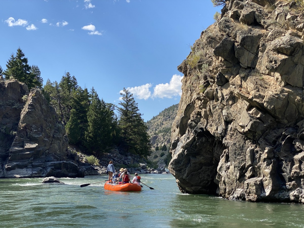 red raft on a river with cliffs fun things to do near yellowstone rafting