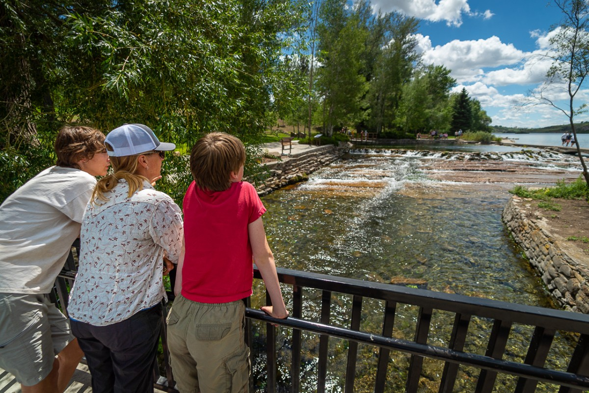 people viewing the Giant Spring in Giant Springs State Park from a bridge on the drive from glacier national park to yellowstone